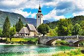 Bohinj Lake, Church of St John the Baptist with bridge. Triglav National Park, Julian Alps, Slovenia.