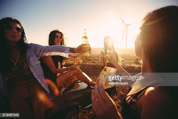 Boho amigos Tostar ao pôr do sol com cerveja e pizza