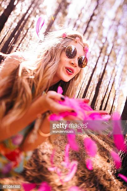 Boho girl blowing pink feathers in a forest