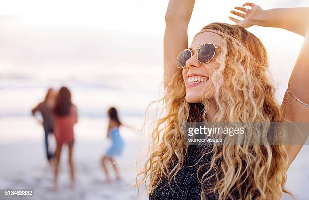 Boho-Mädchen Tanzen am Strand mit Freunden am Strand