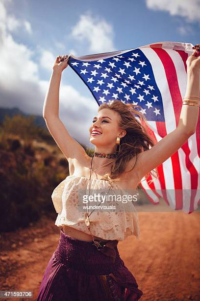 Boho girl flying an American flag on a country road