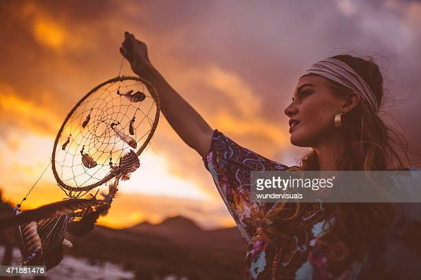 Boho girl holding up a dream catcher on summer evening