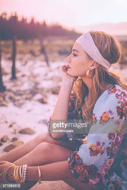 Boho girl in a headband sitting in nature