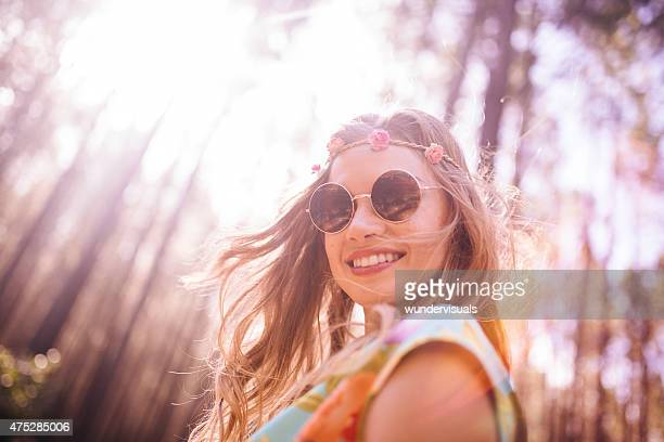 Boho girl in flower headband and round sunglasses