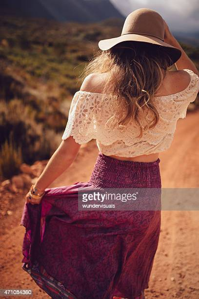Boho girl in purple skirt walking down a dirt road
