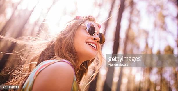 Boho ragazza in occhiali da sole in una foresta estate