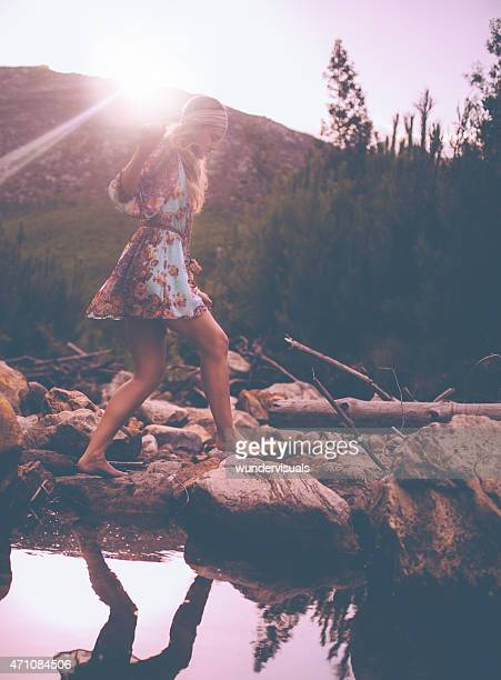 Boho girl in vintage dress stepping over stones at lake