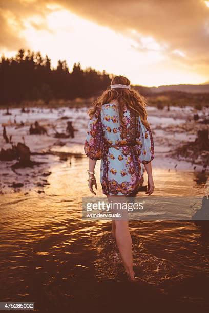 Boho girl in vintage floral dress walking through a lake