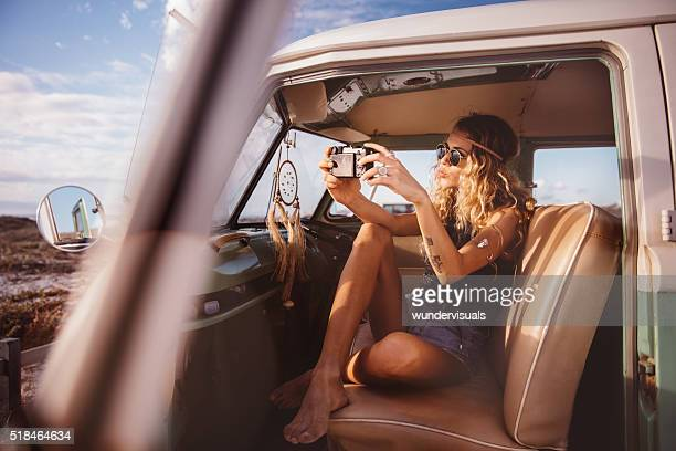Boho girl in vintage van taking road trip selfie