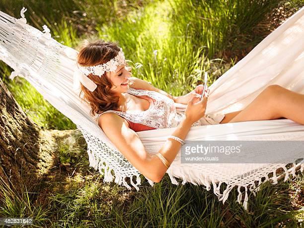 Boho-girl lying in einem Sommer Hängematte mit Ihrem Telefon