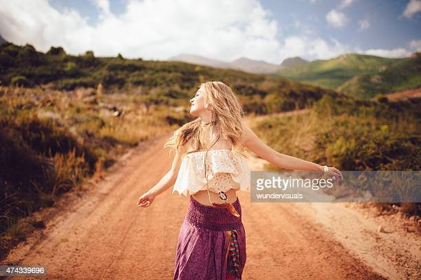 Boho girl on a country dirt road being joyful