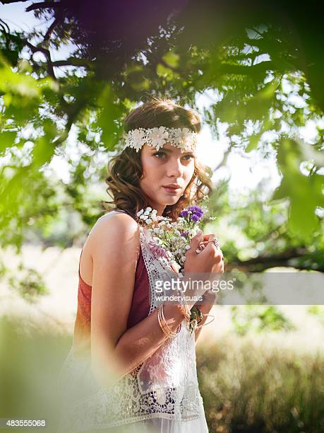 Boho girl surrounded by leaves in a summer park