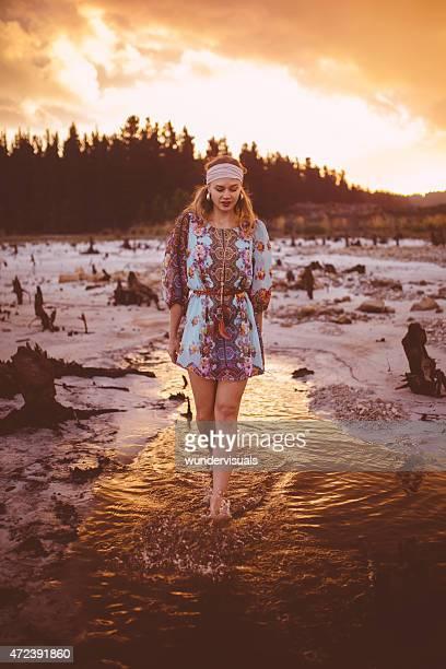 Boho girl walking in a lake at sunset