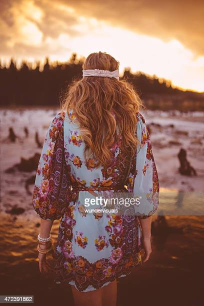 Boho girl walking in nature at sunset