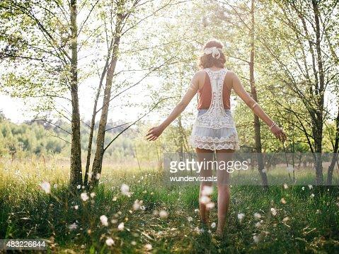 Boho girl walking through summer park feeling free