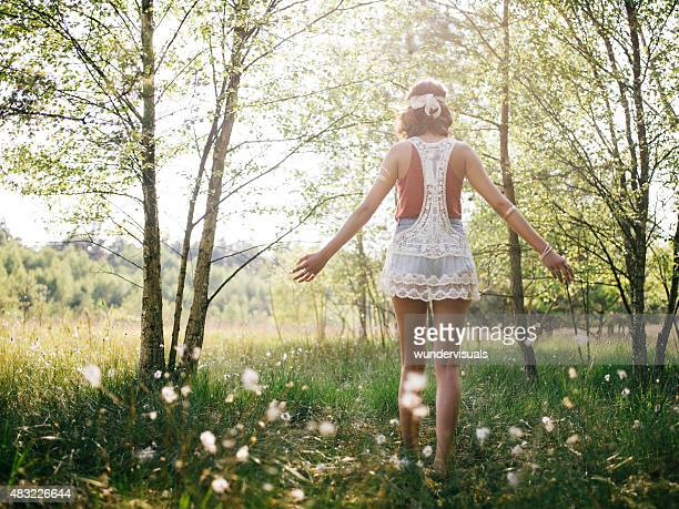 Boho girl walking through summer park feeling free