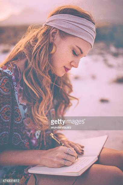 Boho girl writing in her journal while surronded by nature