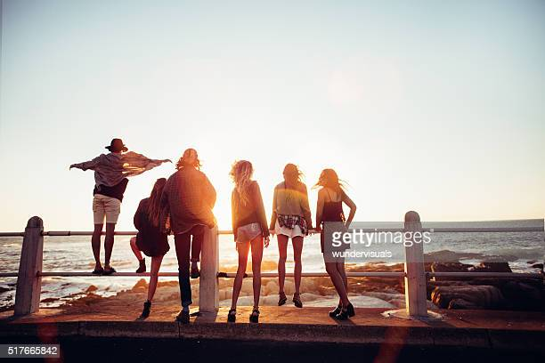 Boho style friends reaching the beach on a road trip