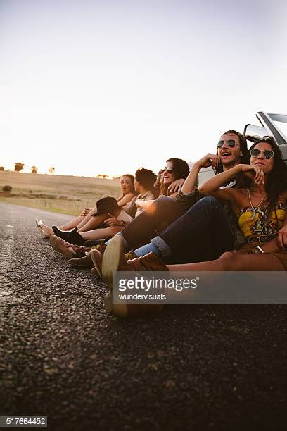 Boho style friends relaxing in a country road at sunset