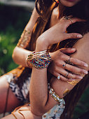 Cropped shot of a boho style girl sitting outdoors wearing many bangles and rings