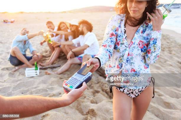 Boho woman using credit card for contactless payment on beach