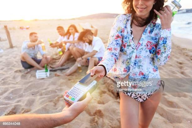 Mujer Boho con tarjeta de crédito para el pago sin contacto en la playa