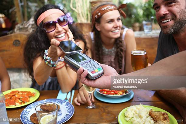 Boho woman using smart phone for mobile payment in restaurant