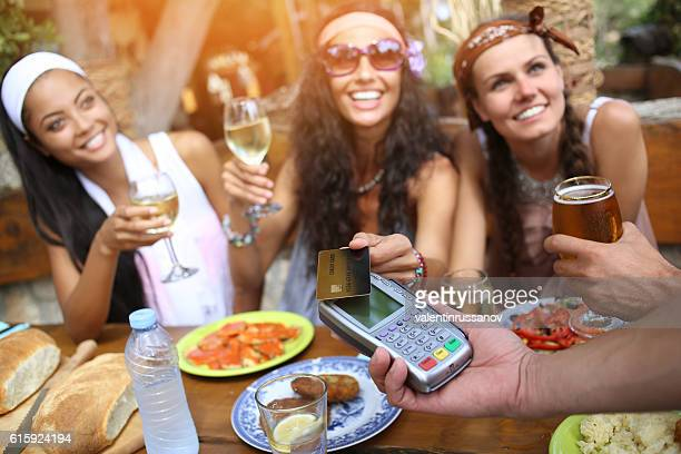 Boho women using credit card for contactless payment in restaurant