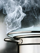 Boiling pot of water, steam rising through lid, close-up