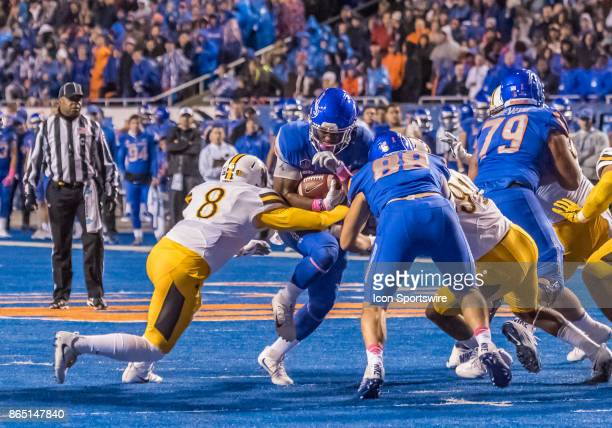 Boise State Broncos quarterback Montell Cozart squeezes some yards past Wyoming Cowboys linebacker Jalen Ortiz while Boise State Broncos tight end...