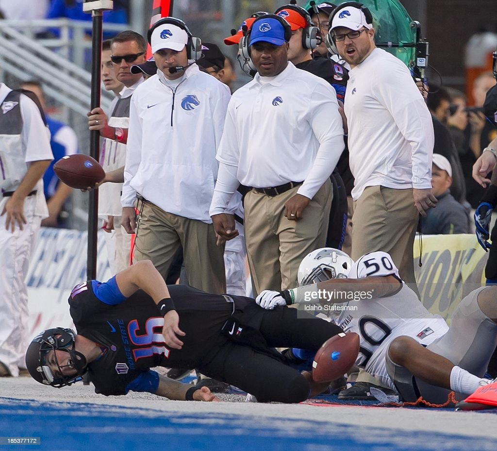 Boise State quarterback Joe Southwick falls along the Bronco sideline tackled by Nevada linebacker Jonathan McNeal at Bronco Stadium in Boise Idaho...