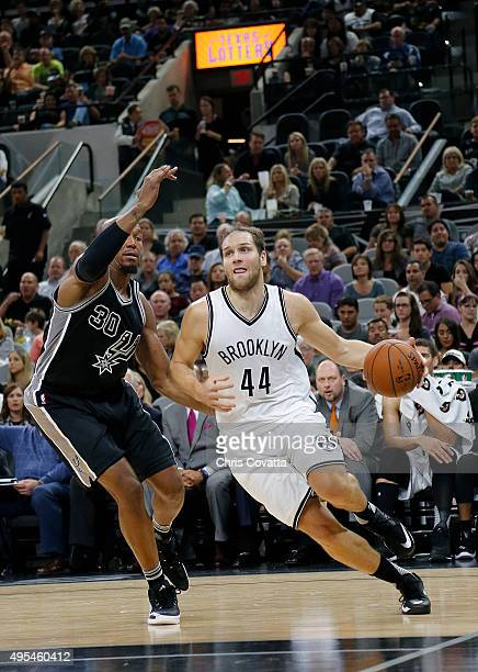 Bojan Bogdanovic of the Brooklyn Nets drives around David West of the San Antonio Spurs at the ATT Center on October 30 2015 in San Antonio Texas...