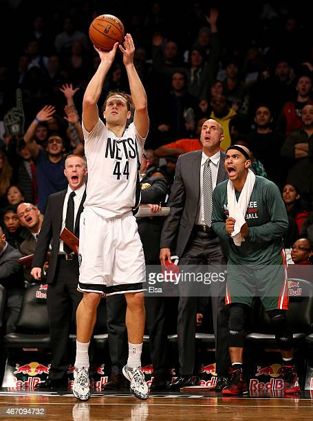 Bojan Bogdanovic of the Brooklyn Nets hits a three point shot as Jerryd Bayless of the Milwaukee Bucks reacts on the bench in overtime at the...