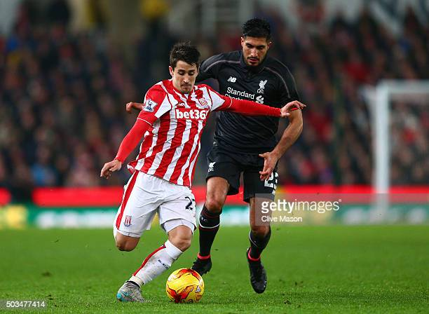 Bojan Krkic of Stoke City is challenged by Emre Can of Liverpool during the Capital One Cup semi final first leg match between Stoke City and...
