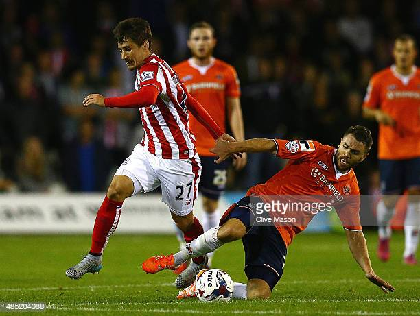 Bojan Krkic of Stoke City is challenged by Josh McQuoid of Luton Town during the Capital One Cup second round match between Luton Town and Stoke City...
