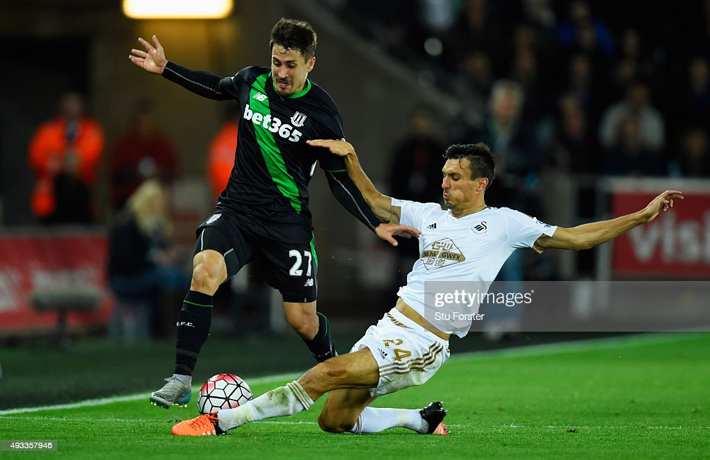 Bojan Krkic of Stoke City is tackled by Jack Cork of Swansea City during the Barclays Premier League match between Swansea City and Stoke City at Liberty Stadium on October 19, 2015 in Swansea, Wales.