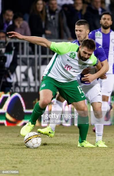 Bojan Sankovic of Ujpest FC tries to tackle Daniel Bode of Ferencvarosi TC during the Hungarian OTP Bank Liga match between Ujpest FC and...
