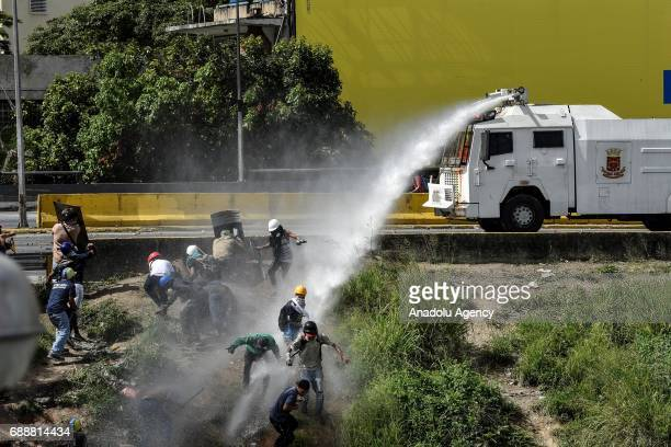 Bolivarian National Guard use water cannon to disperse protesters during a demonstration against Venezuelan President Nicolas Maduro in Caracas on...