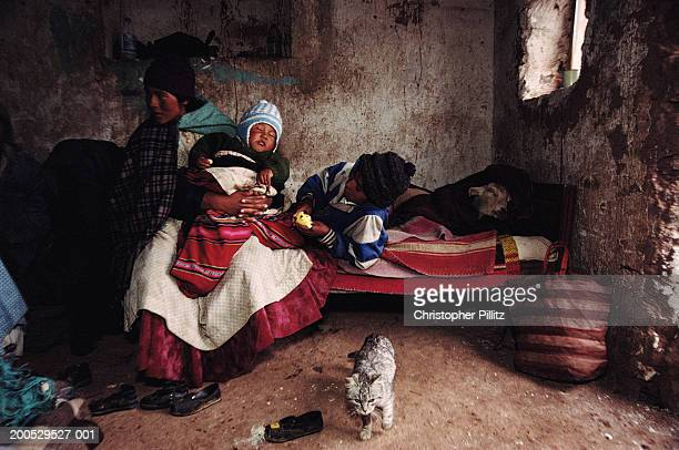 Bolivia, Altiplano, mother and child inside house, cat in foreground