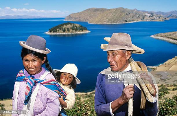 Bolivia, Aymara Indian woman carrying child and grandfather by lake