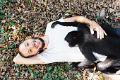 Bolivia, Coroico, portrait of smiling man laying on the ground with black spider monkey on his chest
