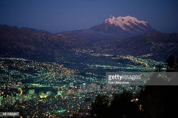 Bolivia La Paz Illuminated cityscape and snow capped peak of Mount Illimani at dusk