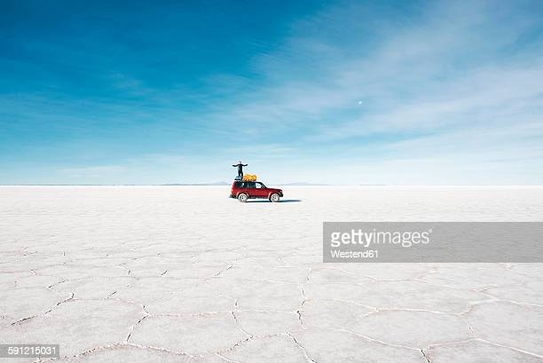 Bolivia, Potosi, man standing on his 4x4 in the Uyuni Salt Flats