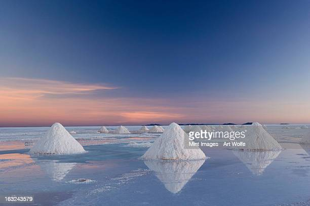 Bolivia, Salar de Uyuni salt flats. Piles of white salt crystals. Harvesting the natural minerals. Sunrise.