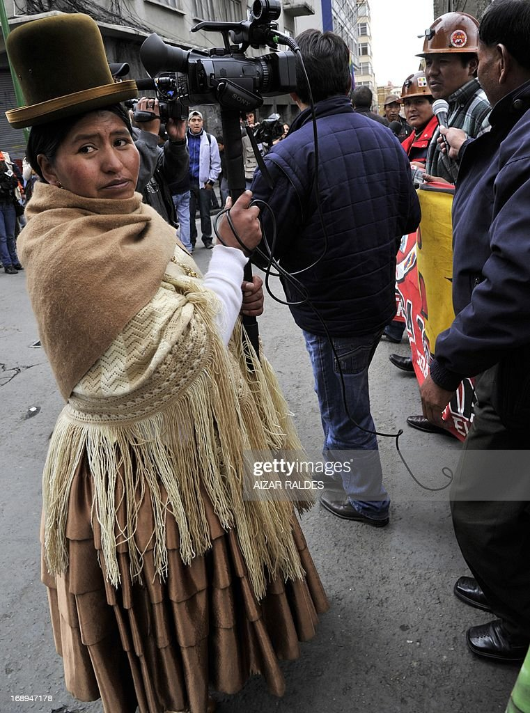 A Bolivian Aymara female cameran covers a workers demonstration on the 12th day of an indefinite strike called by the Bolivian Workers' Central union (COB) to demand the government for a pension equivalent to 100% of their salaries, in La Paz on May 17, 2013. .AFP PHOTO/Aizar Raldes
