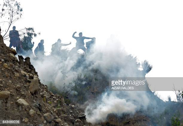 TOPSHOT Bolivian coca growers from Los Yungas region confront riot police agents within a tear gas cloud during a protest against a bill that caps...