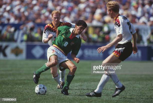 Bolivian footballer Jose Milton Melgar pictured in action with the ball as he attempts to pass German midfielder Stefan Effenberg with fellow German...