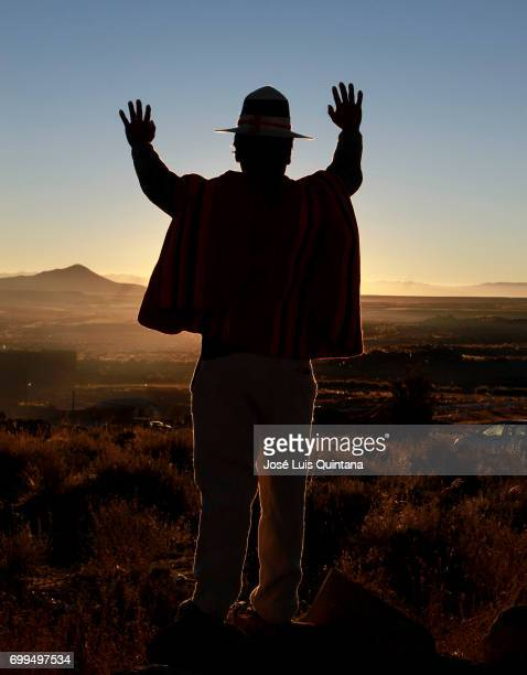 Bolivian indigenous man raises his hands to receive the first sunbeams of the AndeanAmazonic New Year 5525 on June 21 2017 in Orinoca Bolivia