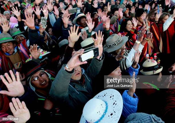 Bolivian indigenous raise their hands to receive the first sunbeams of the AndeanAmazonic New Year 5525 on June 21 2017 in Orinoca Bolivia