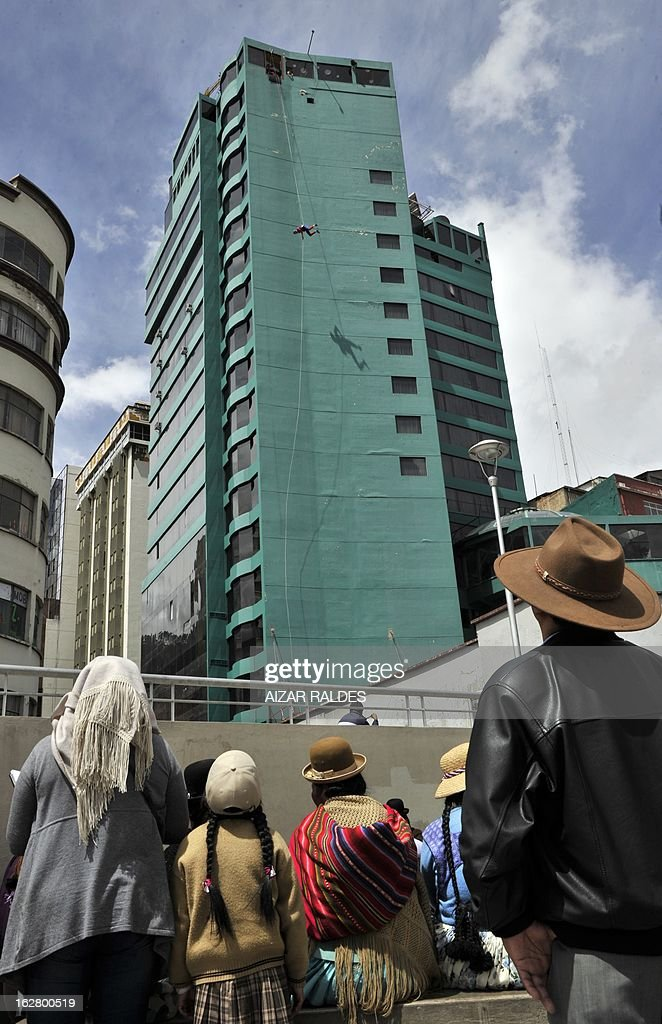 Bolivian indigenous women look as Israeli tourist Shir Cohen practices 'Rap-jumping' at a hotel in La Paz on February 27, 2013. Cohen, 21, went down some 50 meters from the 17th floor of a hotel to a terrace. 'Rap-jumping' is an extreme sport which name comes from the French word 'rapel' -descent of vertical surfaces with ropes and harnesses- and English word 'jumping'. AFP PHOTO/Aizar Raldes
